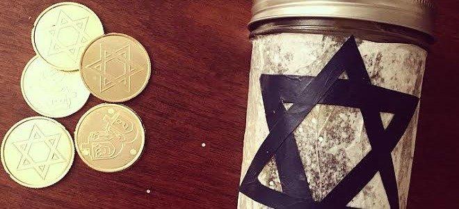 Un tarro de cristal con la estrella de David junto a algunas monedas de chocolate de Hanukkah.